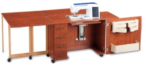 Shown in Sunset Cherry color open, with the machine bed the same height as the surface of the cabinet. Optional machine insert should be ordered for your machine's make and model.  (sewing machine not included)