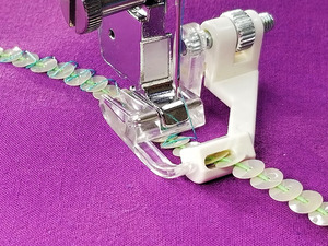 78626: Creative Feet SRSET Sewing Machine Sequins 'N Ribbons Foot. The guide adjusts to your sewing machine needle so you can sew without holding on to the trim!